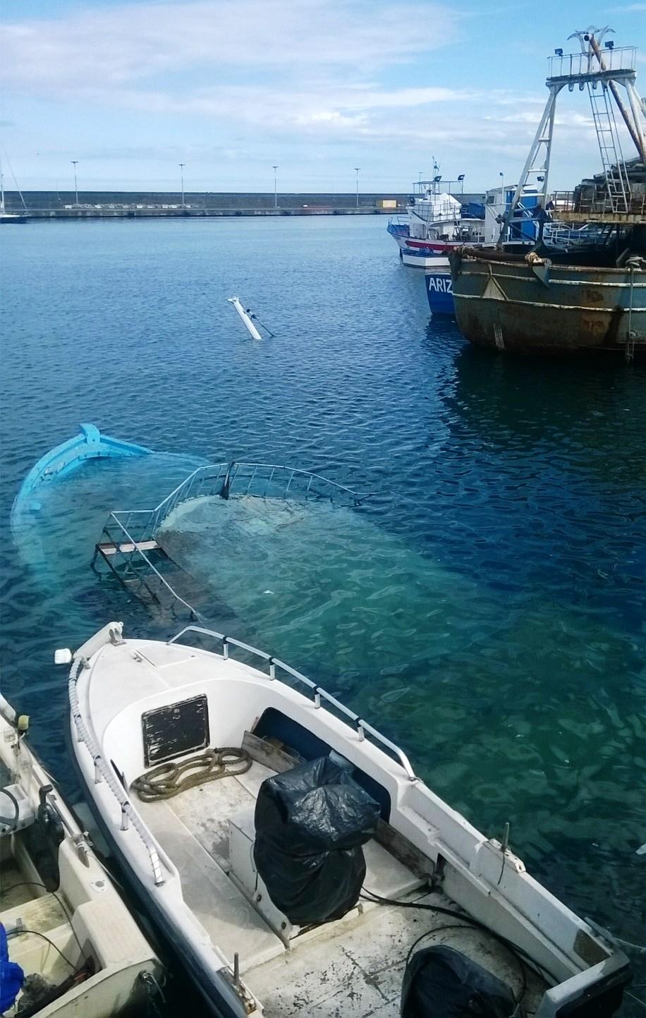 barca affondata e prua di un'altra imbarcazione